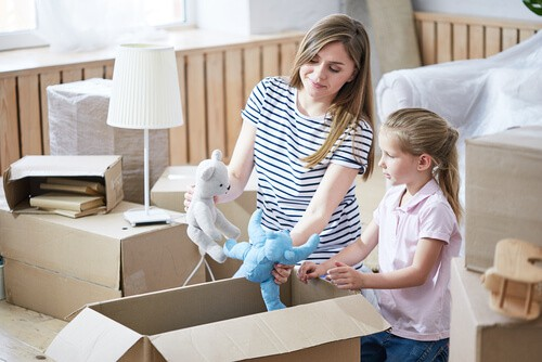 mother and child unpacking box on moving day